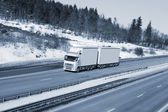 Truck driving on snowy freeway