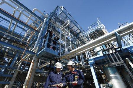 Photo pour Deux ingénieurs, travaillant dans l'industrie pétrolière et gazière, grande construction en arrière-plan - image libre de droit