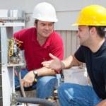 Air conditioning repairmen discussing the problem ...
