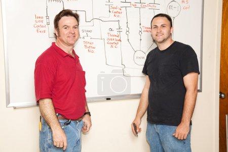 Photo pour Étudiant en génie et professeur passant sur schéma électrique sur le conseil . - image libre de droit