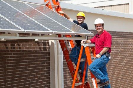 Foto de Electricistas felices empleados para instalar paneles solares energéticamente eficientes en la nueva economía verde . - Imagen libre de derechos