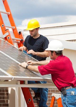 Foto de Electricistas trabajando para instalar paneles solares en un lado de un edificio . - Imagen libre de derechos