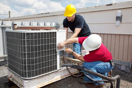 Photo for Two workers on the roof of a building working on the air conditioning unit. - Royalty Free Image