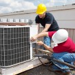 Two workers on the roof of a building working on t...