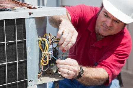 Photo for Air conditioning repairman rewiring a compressor unit. Focus on the man's hands and the wires. - Royalty Free Image