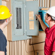 Electricians examining a circuit breaker panel in ...