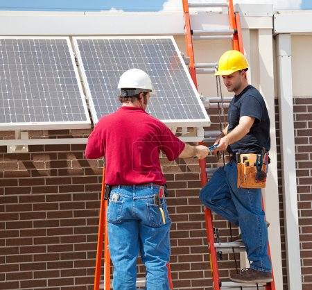 Photo for Two electricians installing solar panels on the side of a building. - Royalty Free Image
