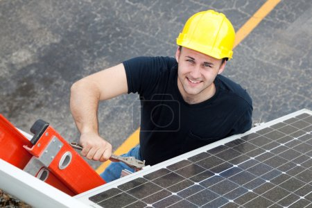 Foto de Joven electricista en una escalera instalar paneles solares. - Imagen libre de derechos