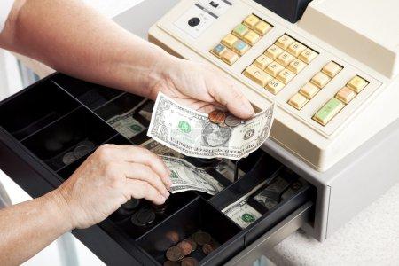 Photo pour Vue horizontale d'un tiroir caisse ouvert comme un caissier fait la monnaie . - image libre de droit