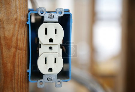 Photo for A 120v duplex electrical receptactle box nailed to a wooden stud. Horizontal with room for text. All logos removed - remaining text is generic. - Royalty Free Image