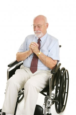 Photo for Senior man in wheelchair prays to recover his health. Isolated on white. - Royalty Free Image