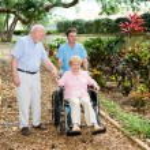Senior woman in a wheelchair being walked through ...