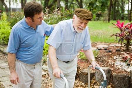 Photo for Senior man struggling to us a walker. His adult son is helping him. - Royalty Free Image