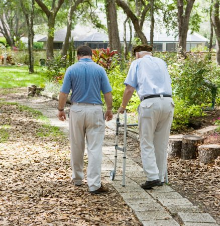 Photo for Father and son strolling through the garden together. The father is in a walker. - Royalty Free Image