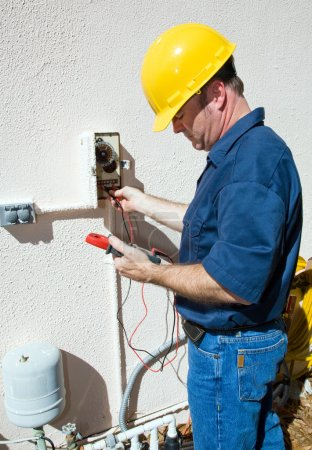 Photo for Electrician repairing a sprinkler pump, testing to see if it's receiving power. Focus on model. Model is a licensed electrician, working in compliance with na - Royalty Free Image