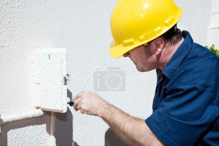 Photo pour Électricien faire réparations à l'intérieur et la boîte électrique à l'extérieur d'une maison. modèle est un électricien et tous les travaux sont exécutés selon l'indu - image libre de droit