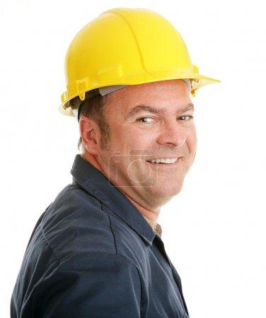 Photo pour Portrait d'un ouvrier de la construction typique souriant, en casque de sécurité sur fond blanc . - image libre de droit