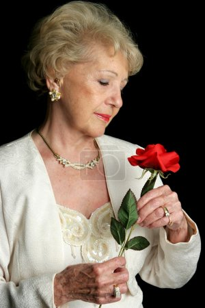 Photo for A beautiful senior lady holding a rose. She is wearing a hearing aid. - Royalty Free Image