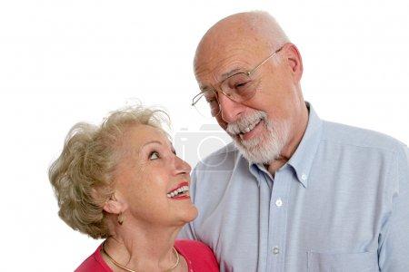 Photo pour Un couple de personnes âgées heureux partage une blague privée ensemble. elle porte un appareil auditif. isolé. - image libre de droit