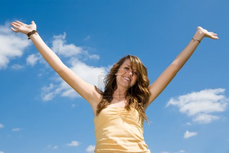 Photo for Beautiful teen girl raising her hands in joy and praise against a blue sky. - Royalty Free Image
