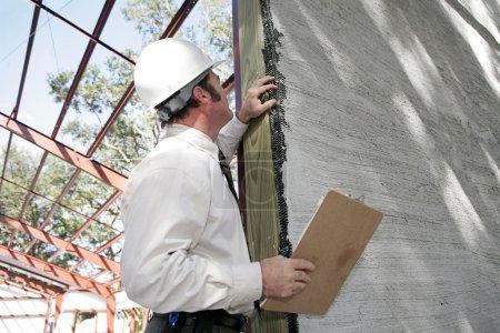 Photo pour Un inspecteur des bâtiments vérifiant sur les stucs incomplète sur les nouvelles constructions. mettre l'accent sur les oeuvres en stuc. - image libre de droit