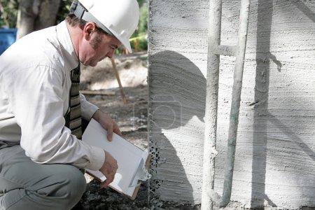 Photo pour Un inspecteur des bâtiments vérifiant la Fondation d'un nouveau bâtiment. - image libre de droit