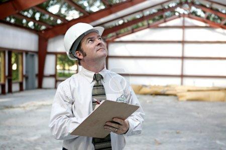 Photo pour Un inspecteur en bâtiment examinant la les poutres d'acier dans un immeuble en construction. vue horizontale. - image libre de droit
