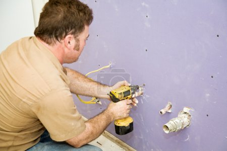 Carpenter Installs Drywall