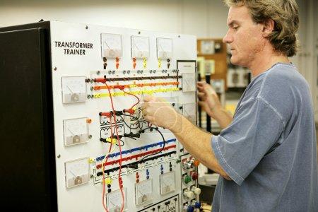 Photo pour Un étudiant en éducation des adultes apprend l'électronique sur un tableau des formateurs de transformateurs . - image libre de droit