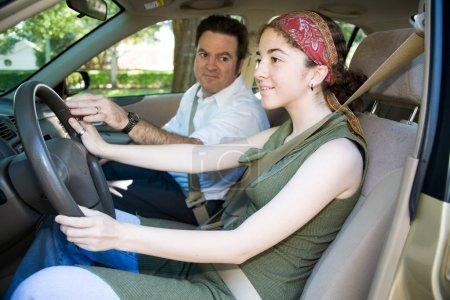 Photo pour Adolescente prenant des leçons de conduite d'un instructeur ou de son père . - image libre de droit