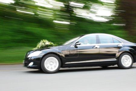 Photo pour Élégante voiture de mariée excès de vitesse avec des fleurs sur le capot. Motionflou - image libre de droit