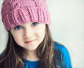Rozkošný usmívající se dívka dítě v růžový pletený klobouk