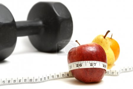 Photo for A few pieces of fruit with a measuring tape and a barbell in the background to conceptualize on fitness. - Royalty Free Image