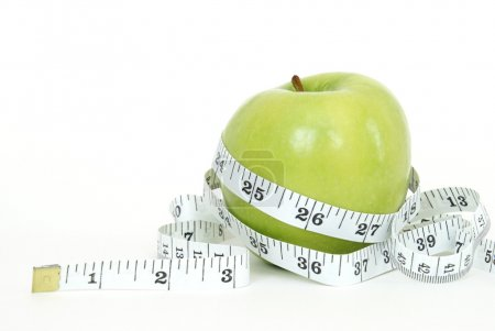 Photo for A green apple with a measuring tape wrapped around it for the concept of dieting. - Royalty Free Image