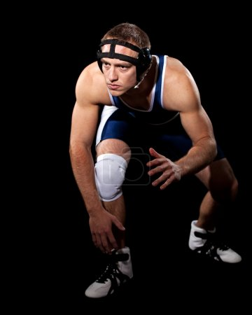 Wrestler in a blue singlet. Studio shot over black.