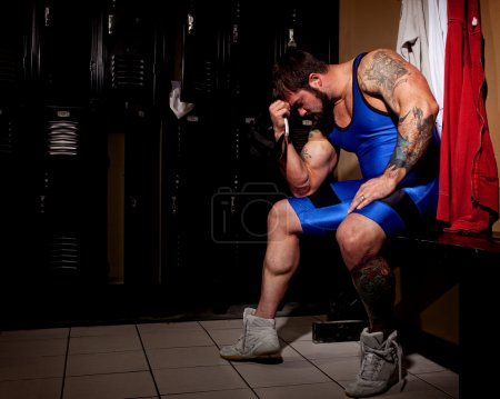 Muscular wrestler in a locker room before or after a match.