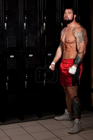 Muscular fighter in a locker room before or after a match.