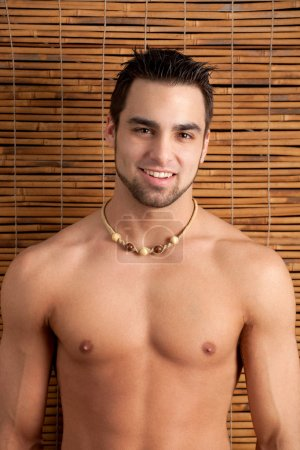 Attractive man, shirtless, in front of bamboo screen.