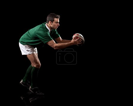 Male rugby player. Studio shot over black.