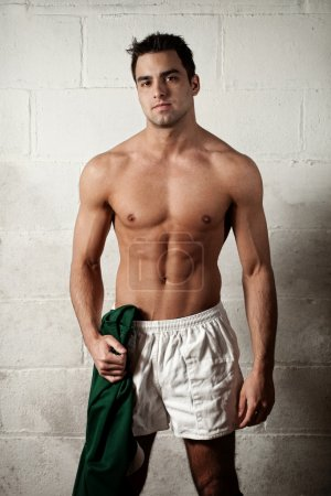 Male rugby player in front of concrete block wall.