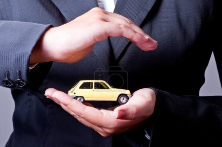 Photo for Two hands facing each other, protect a yellow car. - Royalty Free Image