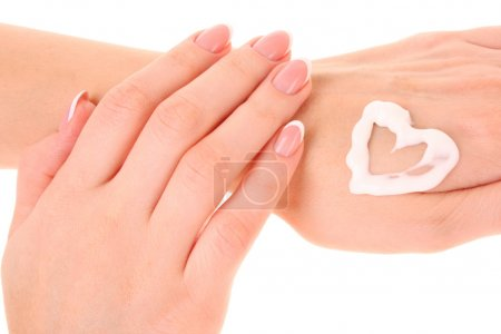 Two woman hands spreading the cream in the form oh heart isolate