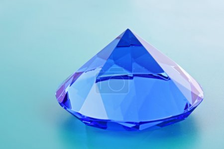 Close up of blue diamond over blue background