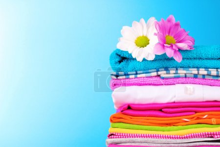 Photo for Pile of colorful clothes and flowers on blue background - Royalty Free Image