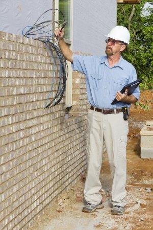 Photo pour Inspecteur des bâtiments vérifiant les fils électriques, lignes téléphoniques, construction charpente, sorties électriques et de plomberie stub - image libre de droit